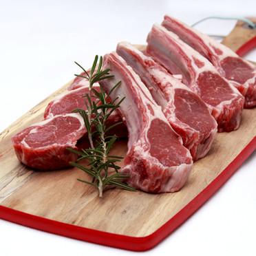 Raw lamb cutlets with rosemary on choppi