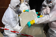 technicians wearing suits removing asbestos