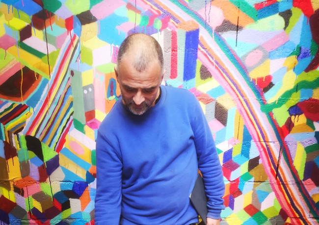 Popay et son chien devant l'immense mur quil a peint pour l'expo