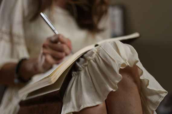 Woman in a white dress sits and writes i