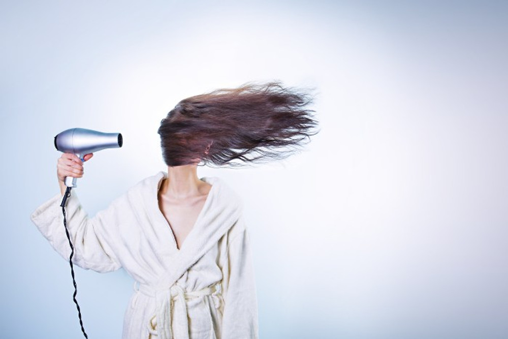 Woman using hair dryer
