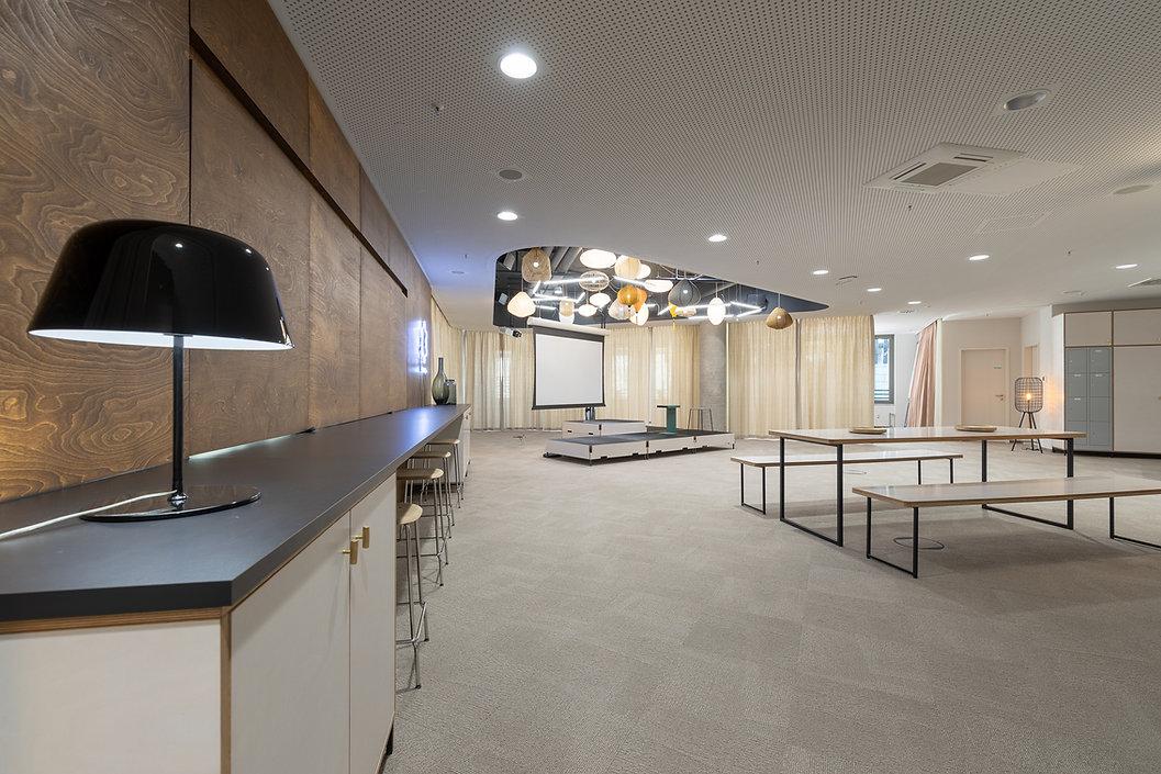 Treffpunkt mit Bar, Arbeitsbereichen, flexibler Bühne und Leinwand für Präsentationen