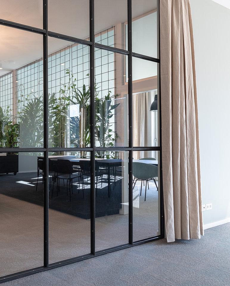 Die Glaswand zwischen Eingang und Besprechungsraum