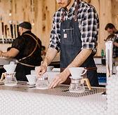 People making coffee using white mugs and glass coffee caraffes