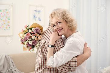110111689-happy-senior-woman-with-flower