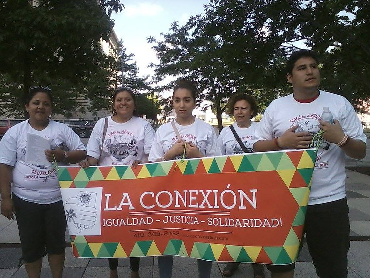 "La Conexion members represent their community in the Cleveland ""Walk for Justice"" - Five members in matching white shirts, carrying a red, green, and yellow banner which reads ""La Conexion - Igualdad - Justicia - Solidaridad!"""