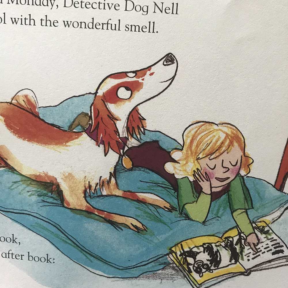 A girl and a dog lay together reading a book.