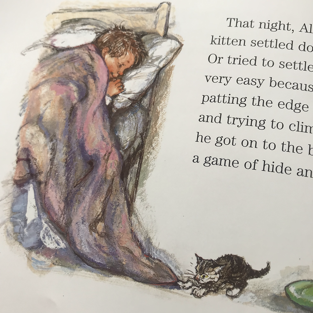 A boy lays in bed while a kitten plays with the bedcovers.