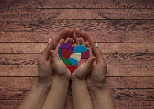 Autism awareness concept with heart of colorful pieces. Woman's and child's hands holding a multicol