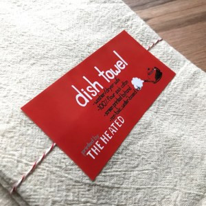 close up of branded sticker for The Heated's dish towel