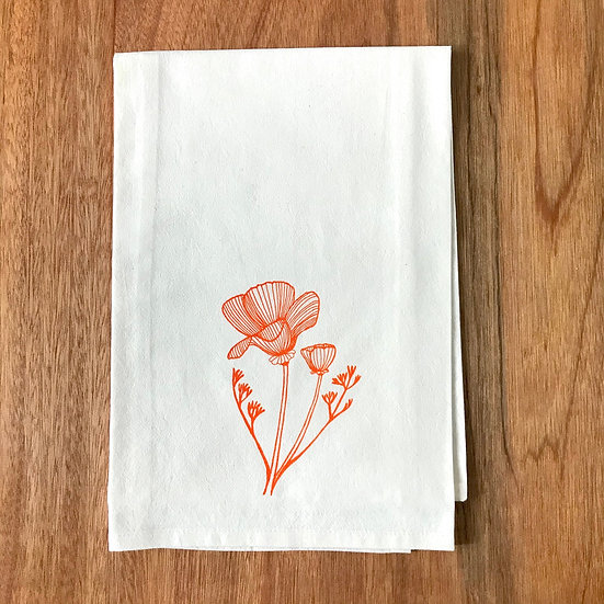 California Poppy design printed in orange ink on a tea towel on wood background