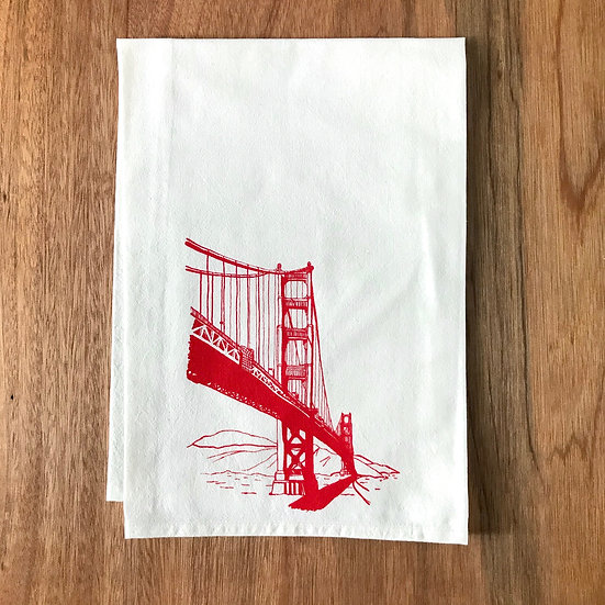 Golden Gate Bridge design printed in red on 100% flour sack cotton tea towel on wooden background.