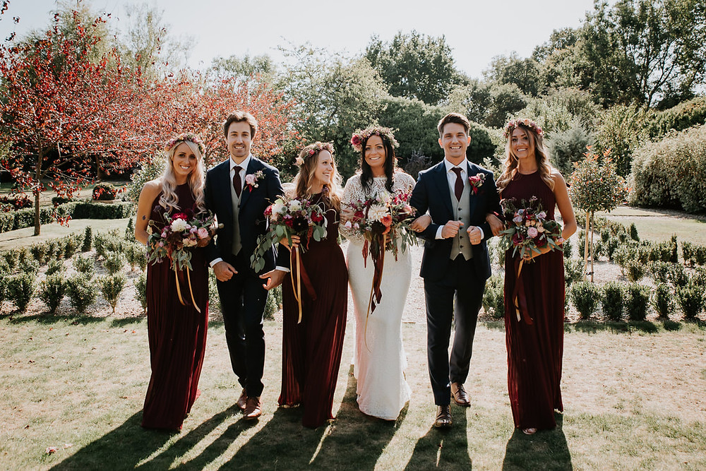 Bridesmaids in burgundy dresses with floral crowns, wedding bouquets with dahlias, natural and rustic wedding flowers,  burgundy wedding colour scheme for a sunny September wedding in Kent by Fig & Flower Wedding florist.