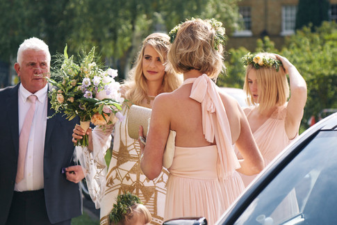 Bride in White and Gold Dress holding Orange and Lilac Hand Tied Bouquet with Bridesmaids in Pink Dresses