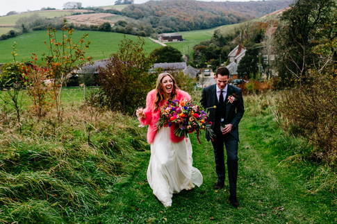 Groom and Brunette Bride in Bright Pink Fur Jacket holding Vibrant Wildflowers