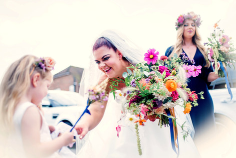 Bride holding Vibrant Wildflower Foliage Bouquet with Flower Girl and Bridesmaid in Floral Crown Hairstyles