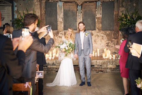 Bride in White and Gold Dress holding Orange and Lilac Hand Tied Bouquet with Groom in Grey Suit in Chapel Wedding Venue