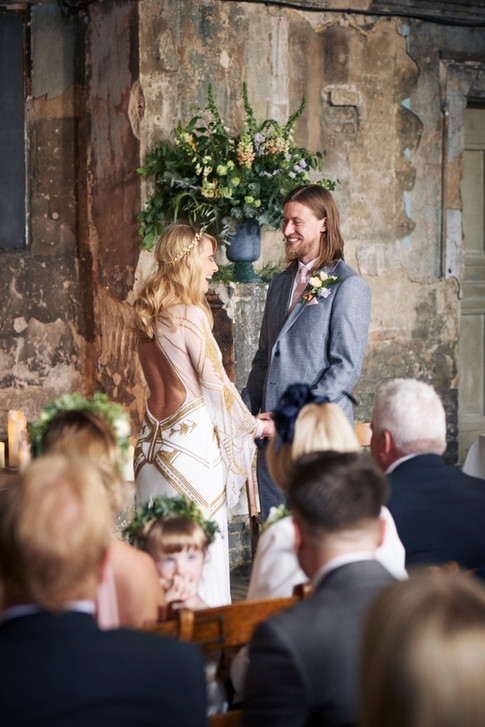 Wildflower Foliage in Wedding Urn behind Groom in Grey Suit and Bride in White and Gold Dress