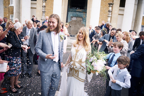 Bride in White and Gold Dress holding Orange and Lilac Hand Tied Bouquet with Groom in Grey Suit with guests outside Chapel Wedding Venue