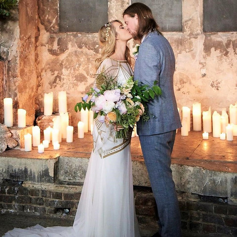 Bride in White and Gold Dress holding Orange and Lilac Hand Tied Bouquet with Groom in Grey Suit in Chapel Wedding Venue kissing