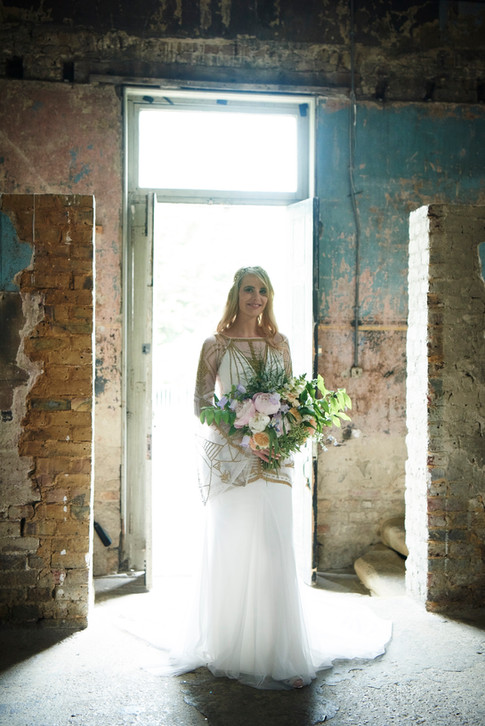 Bride in White and Gold Dress holding Orange and Lilac Hand Tied Bouquet