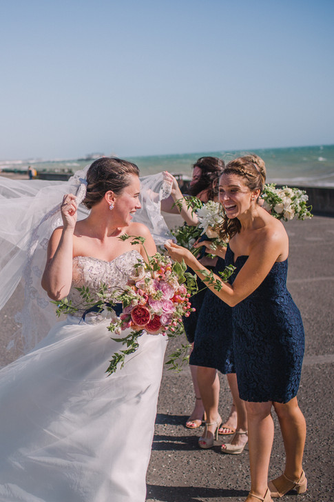 Bridesmaids in Navy Blue Dresses and Bride in Strapless Wedding Dress on Seafront Promenade