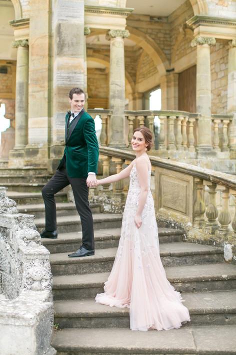 Bride in Romantic Floral Wedding Dress and Groom in Velvet Jacket  on Italian Courtyard Wedding Venue Steps