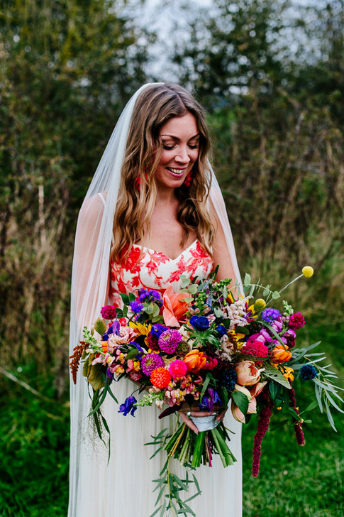 Brunette Bride holding Vibrant Wildflowers in Wedding Bouquet