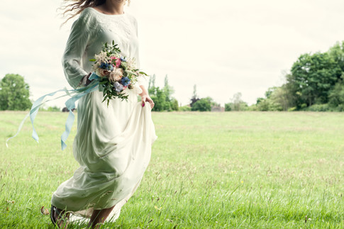 Bride In Field holding Blue Wildflower Bouquet with Long Ribbons