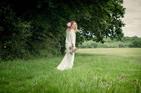 Bride In Field holding Pink and Orange Wildflower Bouquet with Long Ribbons