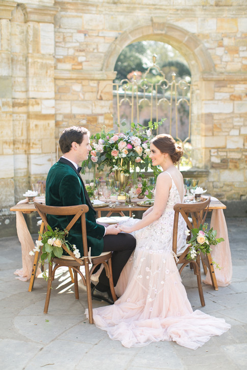 Bride and Groom sitting on Wooden Crossback Chairs with Hand Tied Peach Peonies