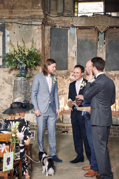 Wildflower Foliage in Wedding Urn behind Groom in Grey Suit