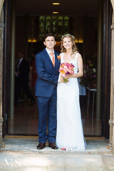 Groom in Navy Blue Suit with Orange Tie and Bride in White Dress holding Hand Tied Wedding Bouquet