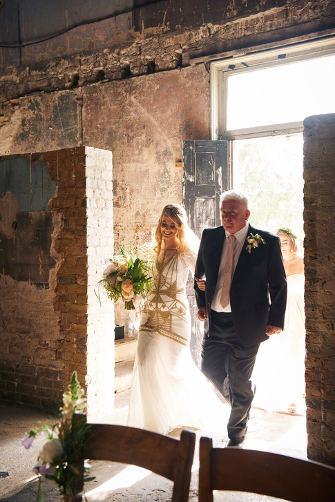 Bride in White and Gold Dress holding Orange and Lilac Hand Tied Bouquet walking into Chapel Wedding Venue