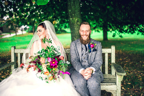 Bride and Groom on Wooden Bench holding Vibrant Wildflower Bouquet