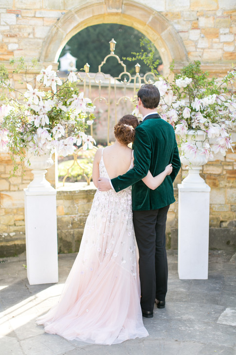 Groom in Velvet Green Jacket and Bride in Romantic Floral Wedding Dress under Courtyard Wedding Venue Arch by Magnolia Flower Outdoor Wedding Decorations