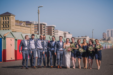 Groom and Groomsmen in Grey Suits with Bridesmaids in Navy Blue Dresses and Bride in Strapless Wedding Dress on Seafront Promenade