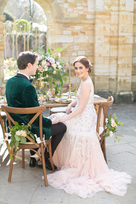 Bride in Romantic Floral Wedding Dress and Groom in Velvet Green Jacket sitting on Wooden Crossback Chairs with Hand Tied Peach Peony Foliage