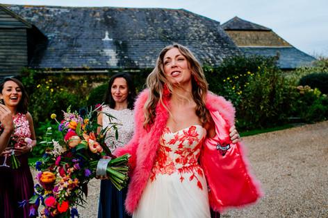 Brunette Bride in Bright Pink Fur Jacket holding Vibrant Wildflowers