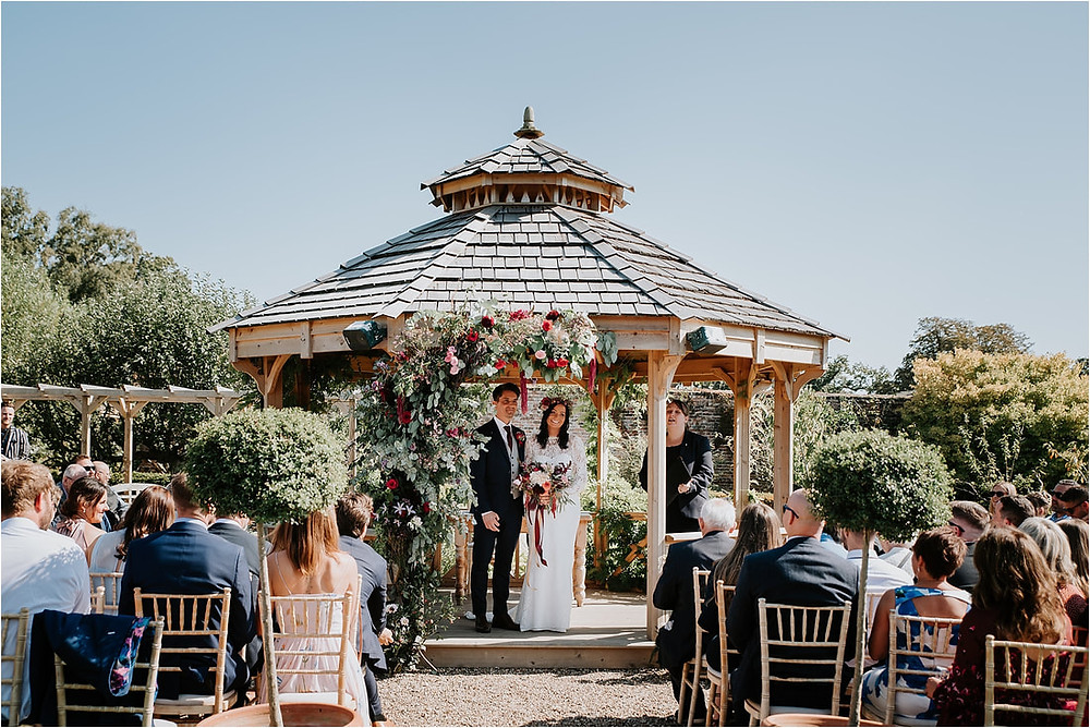 Autumnal wedding in Kent - an outdoor ceremony in  the garden with blush pink and burgundy wedding floral arch, floral ceremony backdrop.