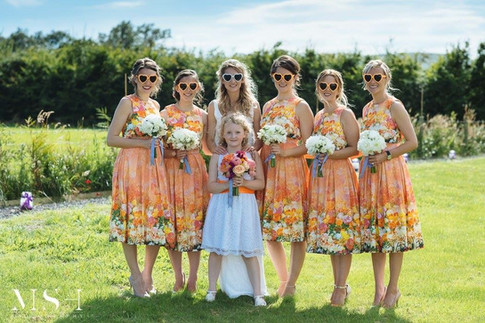 Bridesmaids in Orange Floral Dresses holding White Dahlia Flower Bouquet