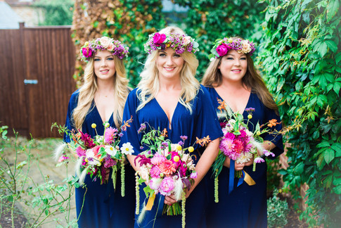 Three Women in Long Royal Blue Bridesmaid Dresses with Floral Crown Hairstyles holding Wildflower Bouquets of Green Amaranthus and Pink Peony Flowers