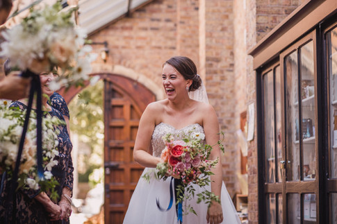 Laughing Bride in Strapless Wedding Dress holding Pink Rose Bouquet