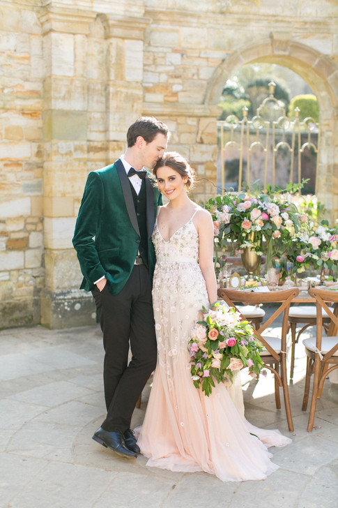 Groom in Velvet Green Jacket and Bride in Romantic Floral Wedding Dress holding Spring Wildflower Bouquet