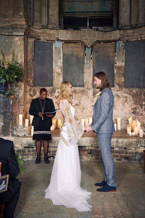 Bride in White and Gold Dress and Groom in Grey Suit at the altar of the Chapel Wedding Venue