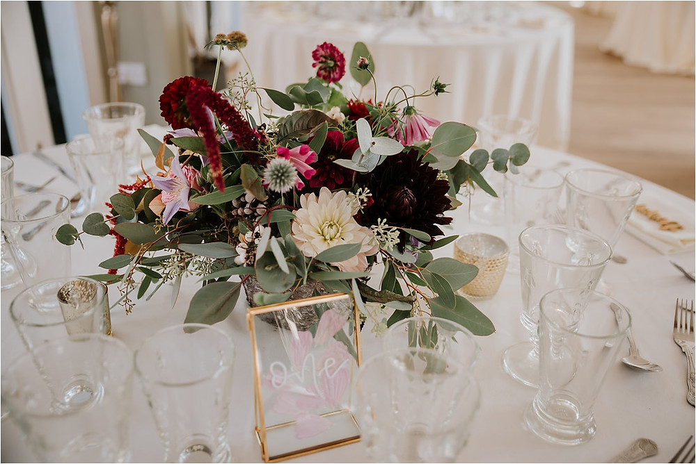 Eucalyptus and grasses, combined with burgundy dahlias, pink cosmos, berries and grasses. Round wedding tables with white table cloths and gold metal table accessories.