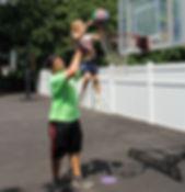 Staff helping camper play basketball
