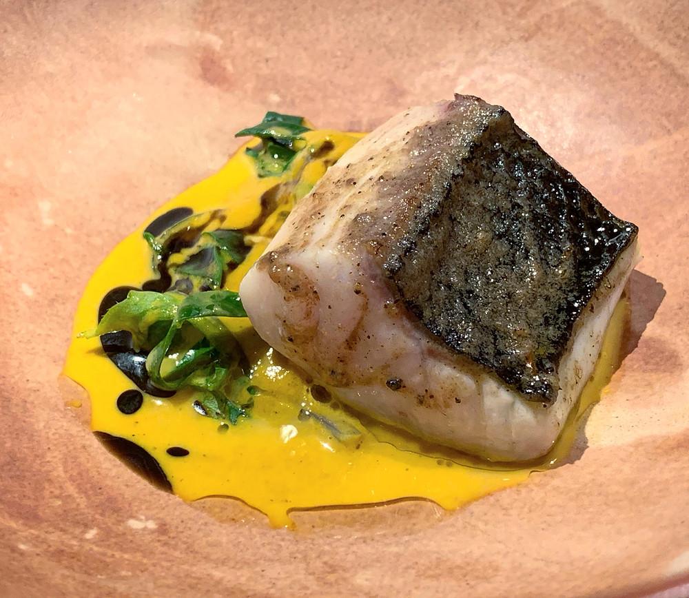 Sea bass in cubeb pepper butter, daikon, saffron, roasted black garlic oil