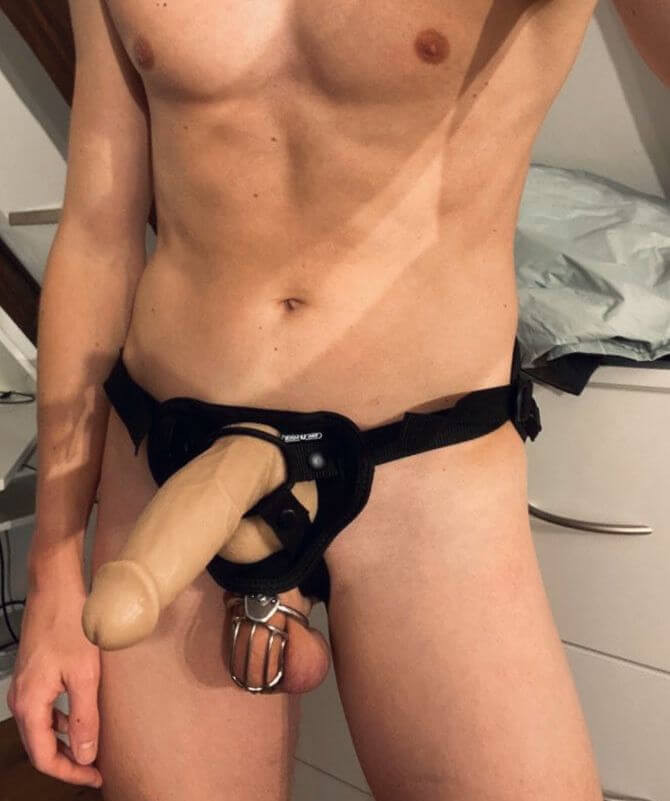 Man wearing cock cage and strap on dildo
