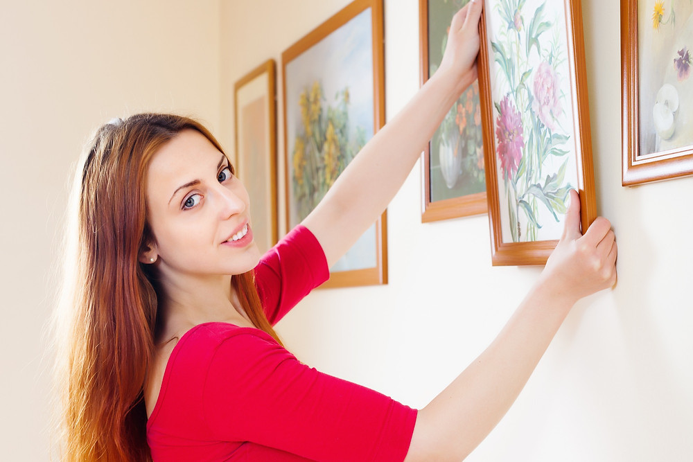 Young woman hanging a picture on the wall